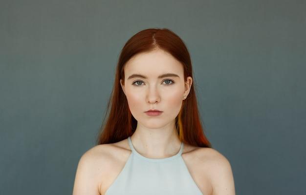 青い壁に立っている深刻なまたは物思いにふける表情で見える青いトップを身に着けている緑色の目を持つ若い柔らかい赤毛の10代の少女の肖像画、彼女の唇はわずかに別れました