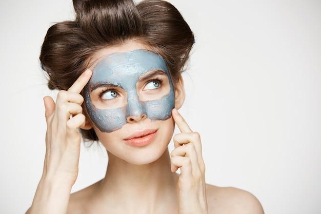 Портрет молодой нежной женщины в бигуди и маска для лица улыбается. концепция красоты и ухода за кожей.