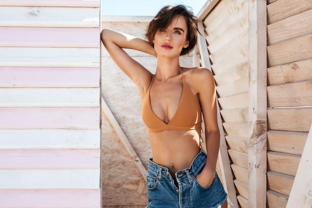 Портрет молодой вдумчивой дамы в бикини и джинсовых шортах, стоящей в раздевалке
