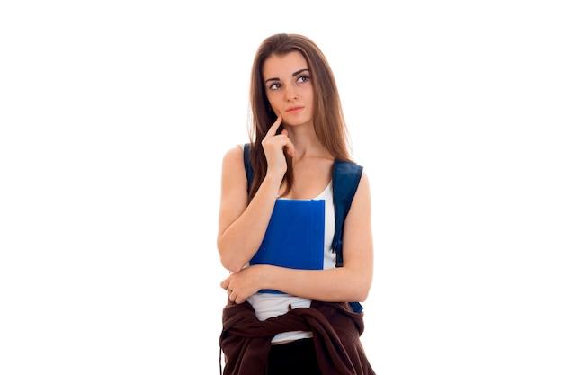 青いバックパックと白い背景で隔離のノートブックのフォルダーを持つ若い思いやりのある学生の女の子の肖像画
