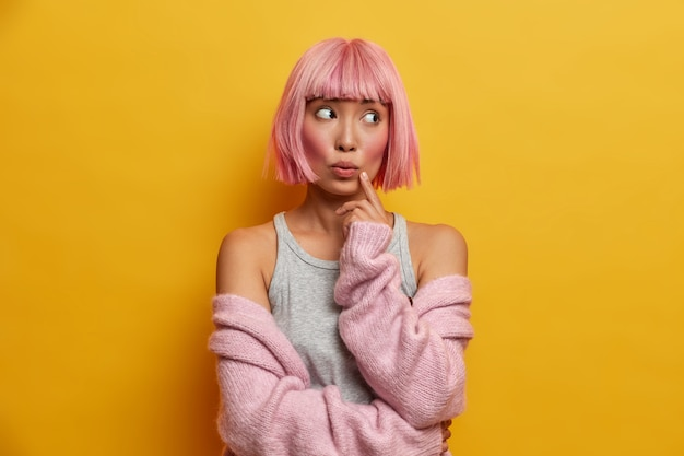 バラ色の髪、顔に指を保ち、脇に不思議に見える、暖かいニットのセーターを着ている若い思慮深く驚いたアジアの女性の肖像画