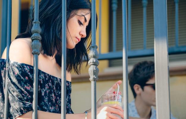 집 계단에 야외에 앉아 손에 레모네이드 잔을 들고 있는 사려 깊은 젊은 여성의 초상화. 젊은 사람들이 문제 개념입니다.