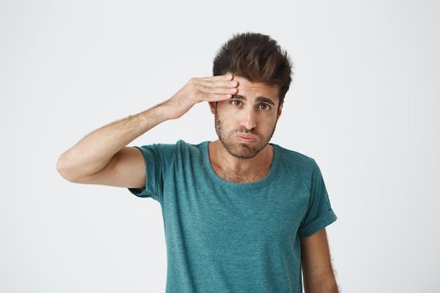 Портрет молодого утомленного кавказского парня нося голубую футболку обтирая лоб с рукой будучи утомленным после сложной тренировки. язык тела.