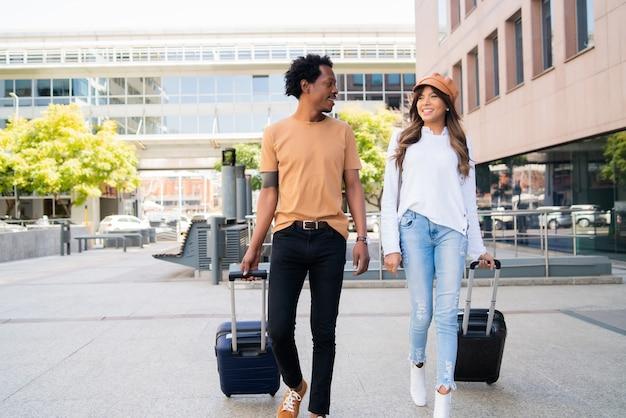 通りを屋外で歩きながらスーツケースを運ぶ若い観光カップルの肖像画。観光の概念。