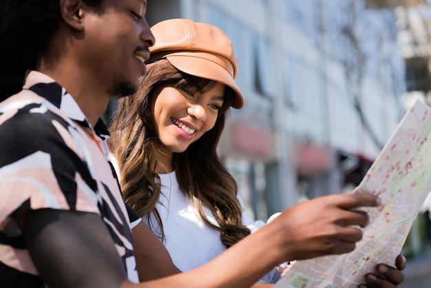 地図を使用して、屋外を歩きながら道順を探している若い観光カップルの肖像画。