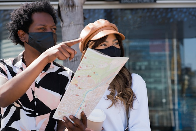 保護マスクを使用して、屋外の道順を探しながら地図を見ている若い観光客のカップルの肖像画。観光の概念。新しい通常のライフスタイルのコンセプト。