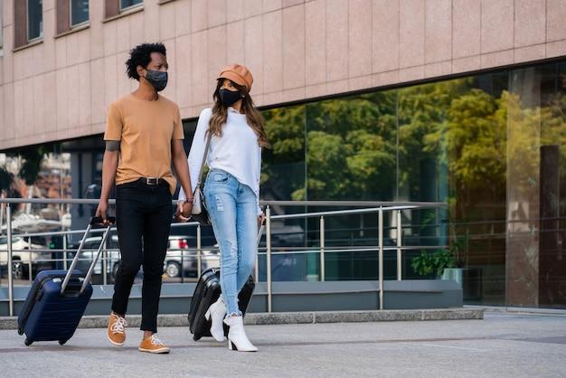 보호 마스크를 착용하고 거리에 야외에서 걷는 동안 가방을 들고 젊은 관광객 부부의 초상화. 관광 개념.