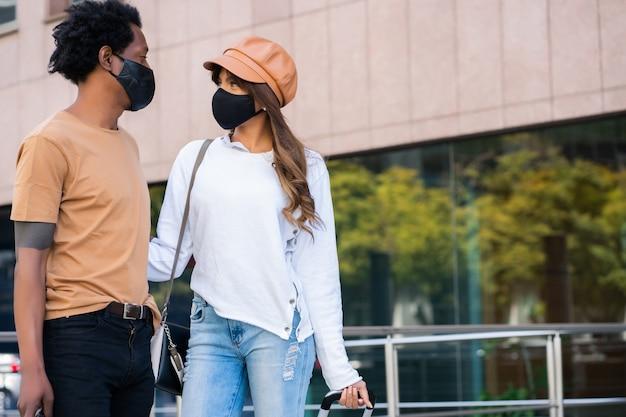 通りを屋外で歩きながら保護マスクを着用し、スーツケースを運ぶ若い観光カップルの肖像画