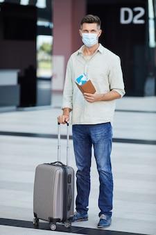 Портрет молодого туриста в защитной маске с багажом и билетами, смотрящего, стоя в аэропорту во время пандемии