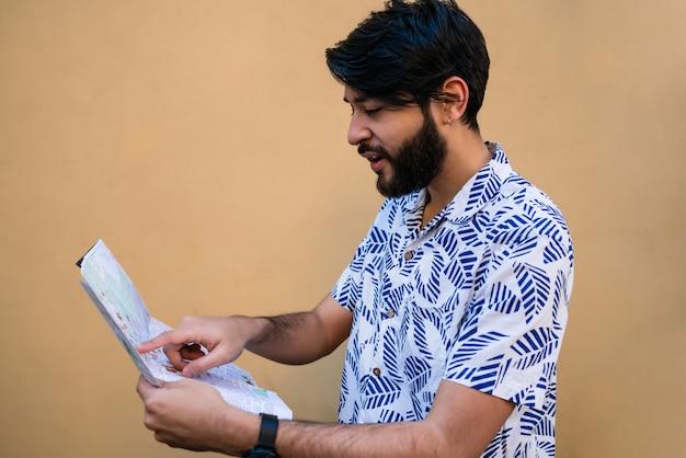 夏の服を着て、黄色に対する方向を探しているマップを保持している若い観光客の男の肖像。
