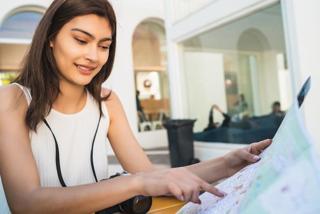 Портрет молодой туристической женщины с картой и поиск направлений, сидя в кафе. концепция путешествия.