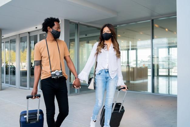 通りを屋外で歩いている間、保護マスクを着用し、スーツケースを運ぶ若い旅行者のカップルの肖像画。観光の概念。新しい通常のライフスタイルのコンセプト。