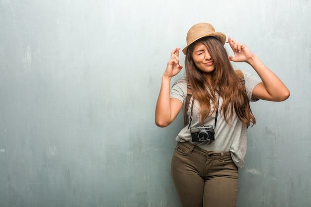 Портрет молодой женщины латинского путешественника против стены, пересекающей его пальцы