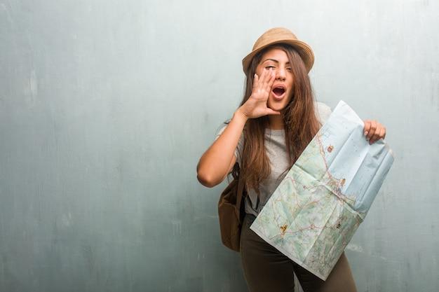Портрет молодой путешественницы латинской женщины против стены кричать счастливым, удивлен предложением или продвижением по службе