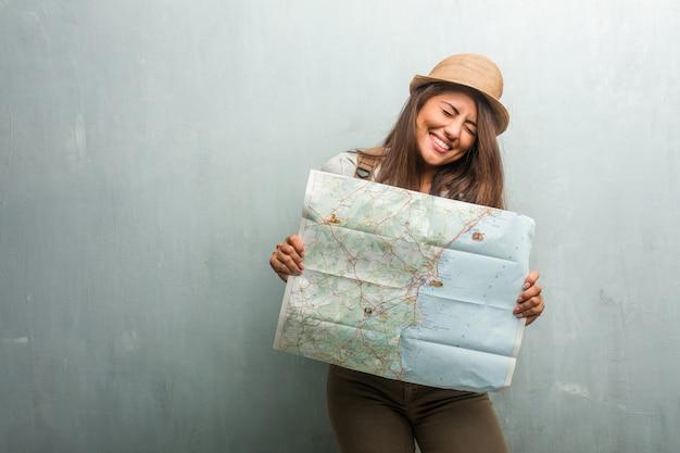 Портрет молодой путешественницы латинской женщины у стены очень рад и взволнован, поднимая руки, празднуя победу или успех, выигрывая в лотерею. проведение карты города.
