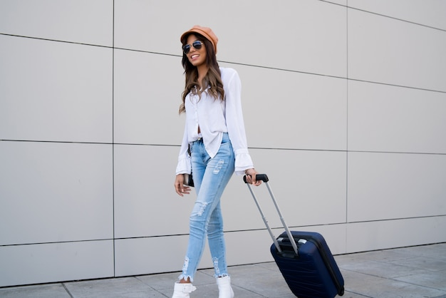 通りを屋外で歩きながらスーツケースを運ぶ若い旅行者の女性の肖像画。観光の概念。