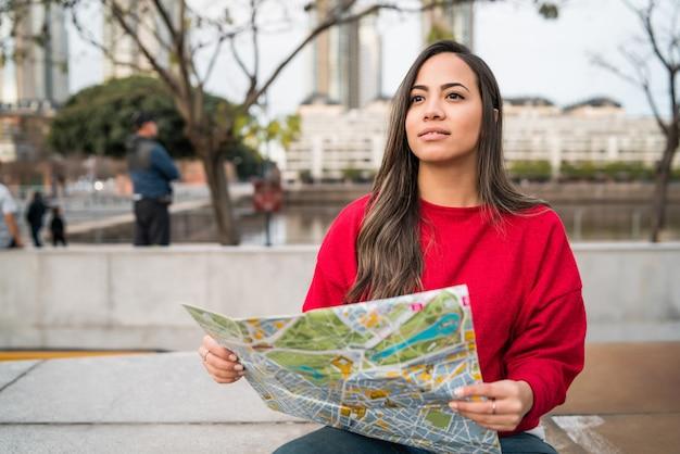 지도를 들고 야외 거리에서 방향을 찾는 젊은 여행자 여자의 초상화. 여행 개념.