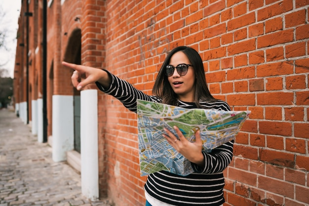 젊은 여행자 여자지도 들고 어딘가에 가리키고 야외 거리에서 방향을 찾고의 초상화. 여행 개념.