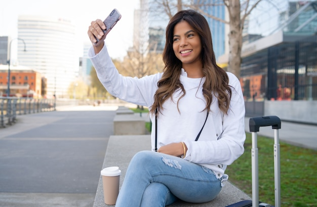 屋外でスーツケースを持って座っている間彼女のmophile電話でselfiesを取っている若い旅行者の女性の肖像画。アーバンコンセプト。観光の概念。