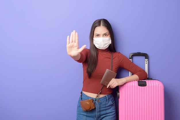 フェイスマスクを持つ若い旅行者の女性の肖像画