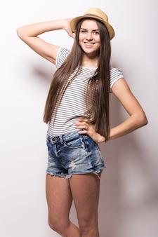 白い壁に分離されたジーンズと麦わら帽子を身に着けている若いトレンディな女性の肖像画
