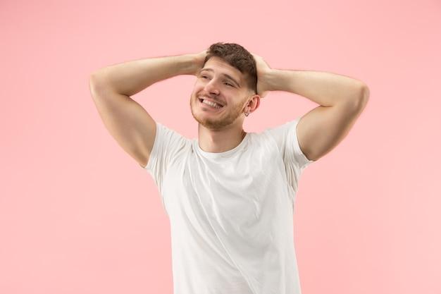 ピンクの背景に若いトレンディな男の肖像画。感情的な表現。