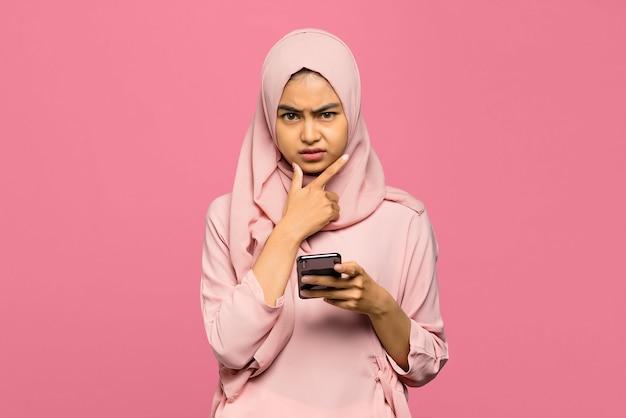 混乱した顔で携帯電話を保持している若い不幸なアジアの女性の肖像画