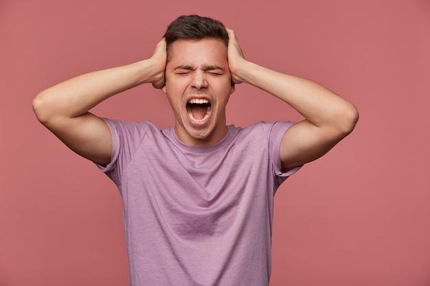 Портрет молодого несчастного привлекательного человека в пустой футболке, стоит на розовом фоне и кричит, держит голову, выглядит сердитым и несчастным.