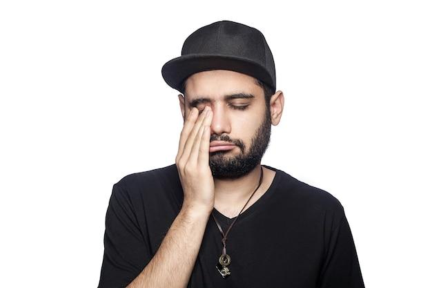 目を閉じて泣いているカメラを見ている黒いtシャツと帽子をかぶった若い不幸な悲しい男の肖像。スタジオショット、白い背景で隔離。