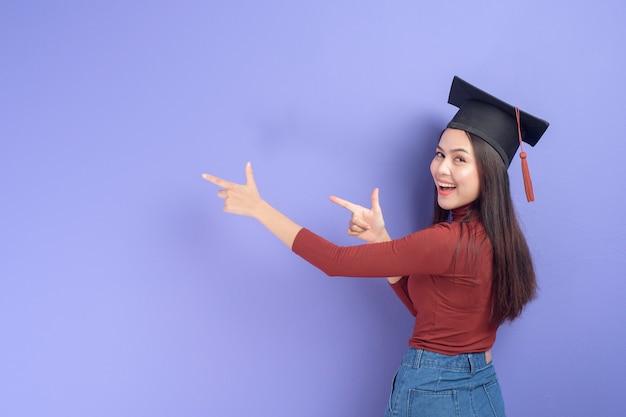 紫色の背景に卒業の帽子を持つ若い大学生女性の肖像画
