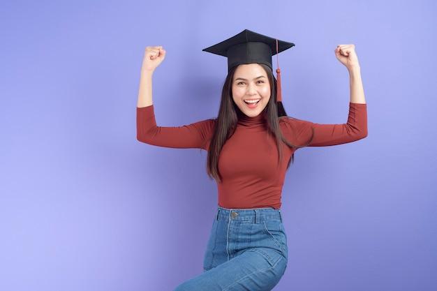 Портрет молодой студентки университета с выпускной кепкой на фиолетовом