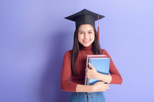 卒業キャップを持つ若い大学生の女性の肖像画