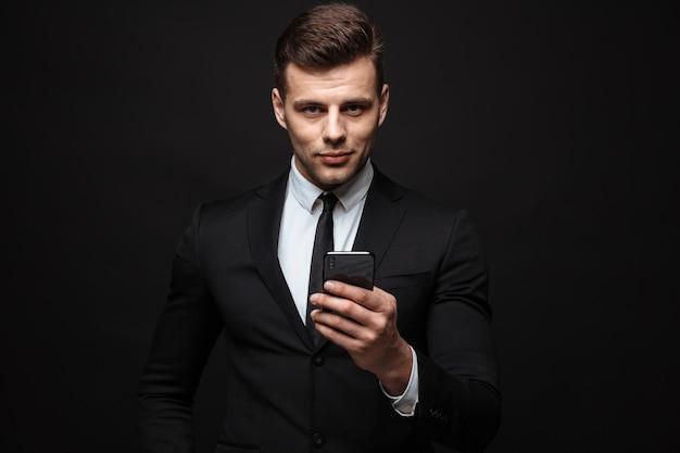 Портрет молодого небритого бизнесмена, одетого в строгий костюм, используя мобильный телефон и смотрящего в камеру, изолированную над черной стеной