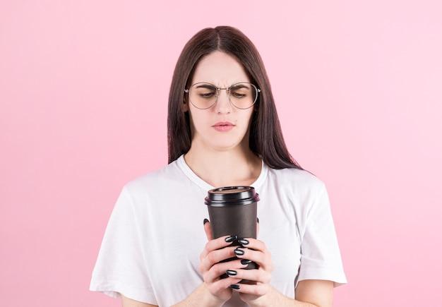 Портрет молодой расстроенной европейской женщины хмурит брови и держит губы сложенными, держит кофе, чтобы продолжить розовое