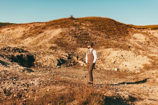 일몰시 자연 속에서 정장에 젊은 빈티지 남자의 초상화