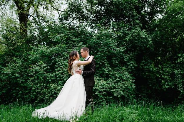 Портрет молодой свадебной пары на природе.