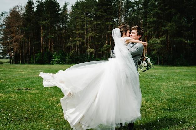 Портрет молодой свадебной пары, целующейся в природе.