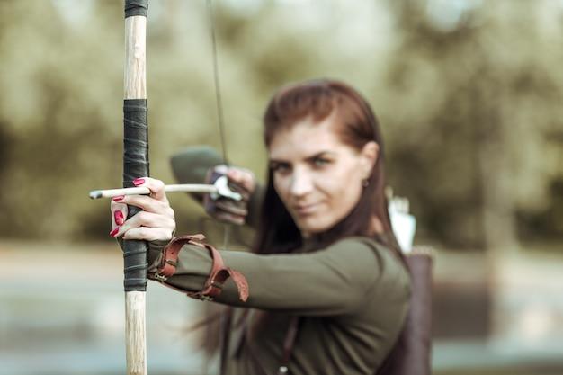 Портрет молодой женщины стрельба из лука на фоне леса