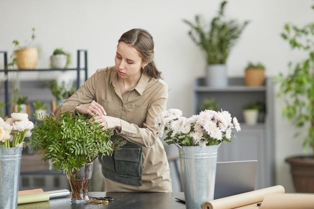 Портрет молодой женщины, составляющей цветочные композиции в мастерской зеленых флористов, копией пространства