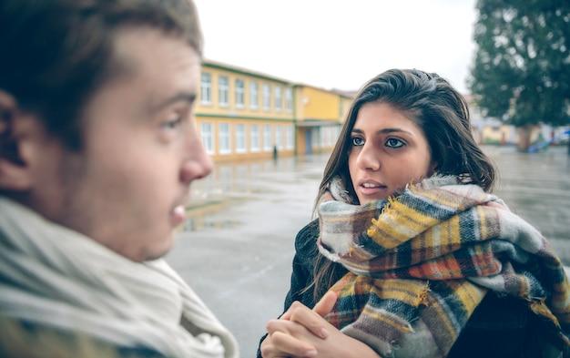 야외에서 힘든 싸움을 한 후 기분이 상한 남자에게 사과를 요청하는 젊은 여성의 초상화. 커플 관계와 문제 개념입니다.