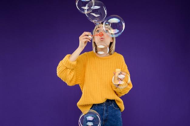 Портрет молодой женщины, пускающей мыльные пузыри над фиолетовой стеной