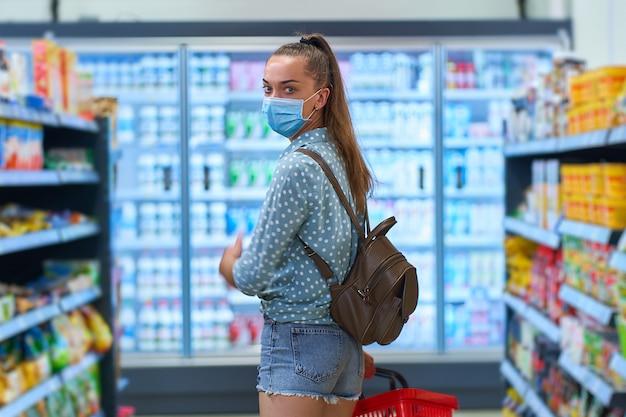 食料品店の棚の間で買い物かごを持つ医療用防護マスクの若い女性バイヤーの肖像画