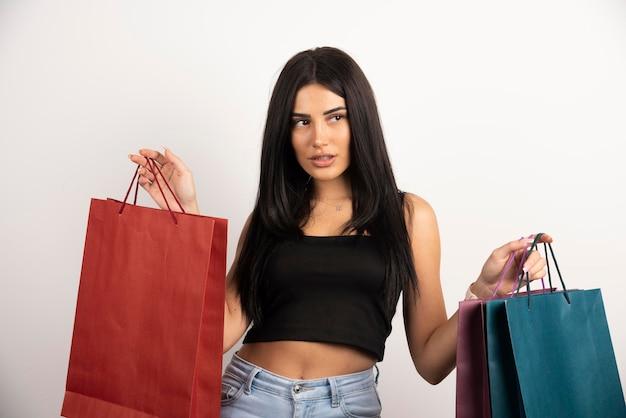 ショッピングバッグを運ぶ若い女性の肖像画。高品質の写真