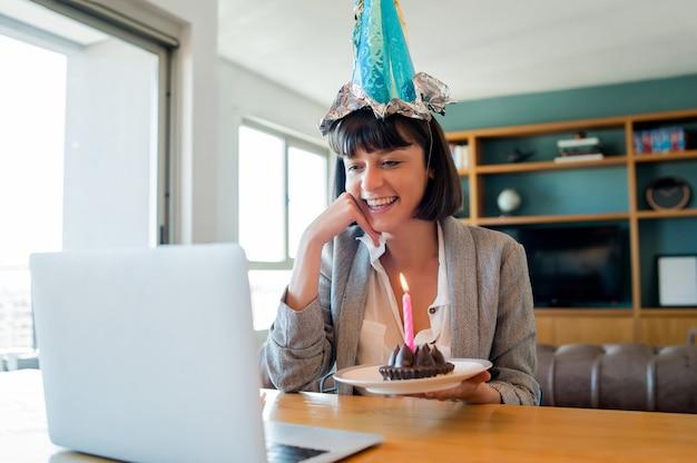 Портрет молодой женщины, празднующей день рождения на видеозвонке с ноутбуком и тортом из дома