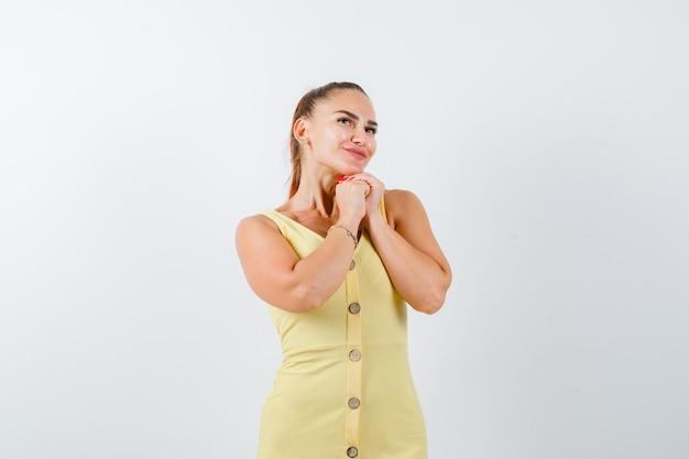 Портрет молодой женщины, взявшись за руки в молитвенном жесте, глядя вверх в желтом платье