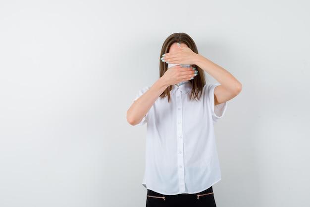 Портрет молодой женщины, закрывающей глаза и рот руками
