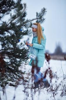 屋外のクリスマスツリーを飾る若い女性の肖像画。クリスマスと冬のコンセプト。