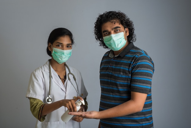Портрет доктора молодой женщины и молодого человека используя или показывая дезинфицирующ гель от бутылки для очищать рук.