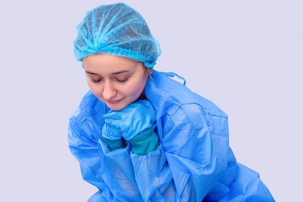 의료 유니폼을 입은 젊은 여성 의사의 초상화 그녀는 손을 모으고 환자를 위해 기도하고 있다