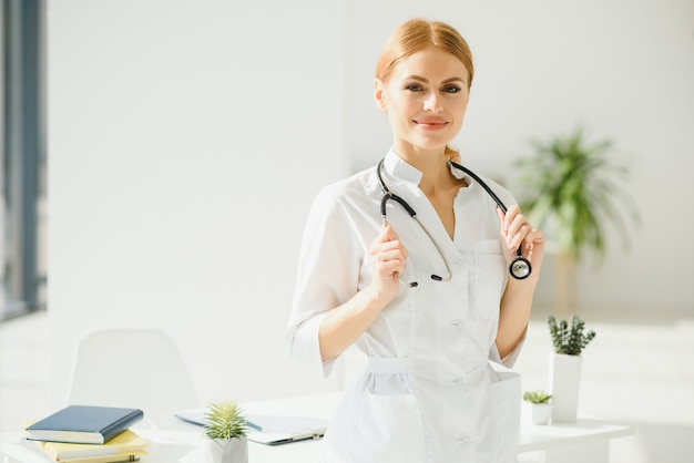 病院に立っている白いコートを持つ若い女性医師の肖像画